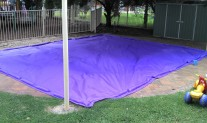 Sandpit cover Lilac with bagged sand weights.